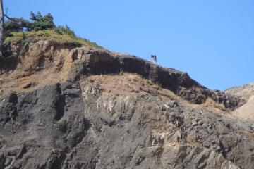 a young man climbing around on top of Roads End headland cliff