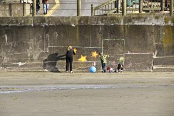 A family attempts to beautify the sea wall at the Nye Beach turnaround. It looks like they are using sidewalk chalk. No permanent harm done.