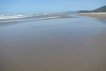 This photo illustrates how wide the beach is at low tide.  The shot is looking north toward the south and north jetties that lead into Tillamook Bay.  Note the two people walking along at the far right.