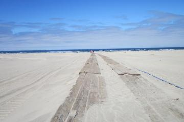 Main wooden timber road built partway across the dunes west of Agate Beach Wayside