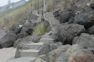 Newly installed spiral concrete steps laid into the rip rap with angle iron railing at north end of mile 234 on Lincoln Beach