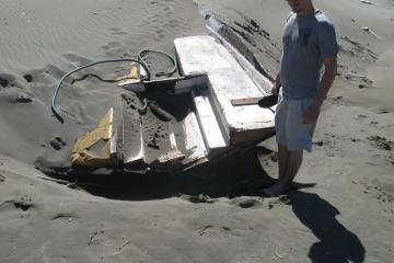 white fiberglass boat bottom less than 20ft long. Partly buried in dry sand high on beach