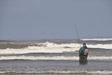 One lone fisherman in the surf.