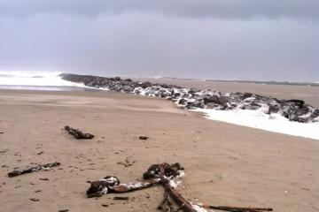 Foam left after a wave surge.  The ebbing tide is brown with flood silt.