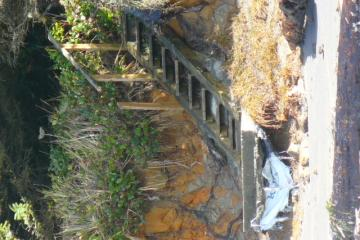 Private beach access stairway to the beach exposed and concrete base undercut by wave action.