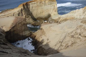 north side of highest point of dune falling into chasm being created by water rushing between Cape and cliff