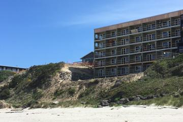 Starfish Manor construction progress shows rock wall on north property line